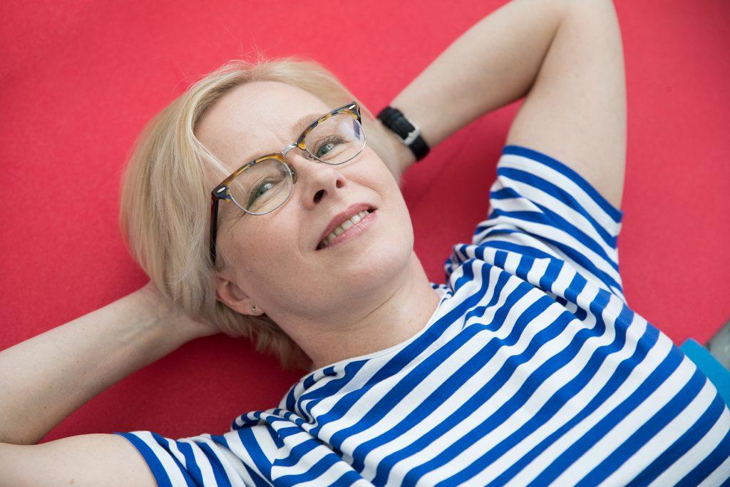 Tutkija Jaana Laitinen katsoo kameraan ja hymyilee.