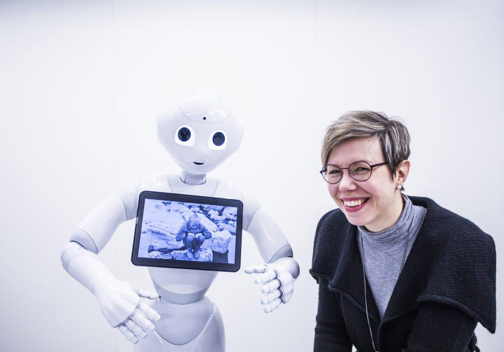 VTT:n tutkija Hanna Lammi ollut seisoo Pepper-robotin vieressä.