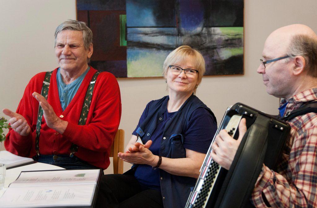 Osmo Anttila ja asumisyksikön esimies Terttu Sulanne osallistuvat  laulutuokioon ja lyövät tahtia käsillään. Jouko Vesa soittaa harmonikkaa.
